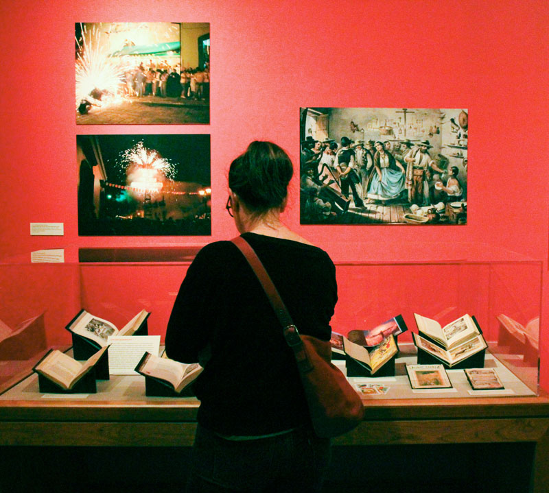 A visitor looks at the collection at the ¡Viva la Fiesta! exhibit.