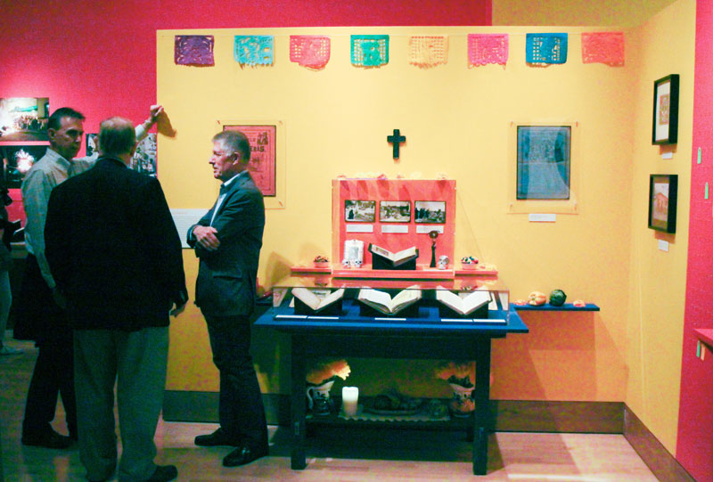 From left, Kenny Grove; Bancroft Deputy Director Peter Hanff; and Bo Wreden chat near the altar at the opening of the exhibit, in The Bancroft Library Gallery.