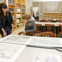 History graduate students Nicole Viglini, left, and Amy O'Hearn discuss Hamilton, in Maps, a pop-up exhibit on display Friday at the Earth Sciences and Map Library. Viglini co-curated the exhibit. (Photo by Jami Smith for the University Library)