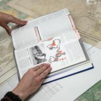 A book lies on maps on a table
